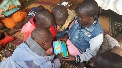 Children at Amani Shelter home using Tablets donated by BSI-Moi University
